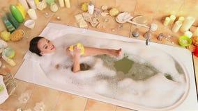 Женщина принимая ванну и chiropody пены пучком мочала в ее ванной комнате акции видеоматериалы