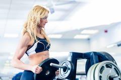Женщина принимая весы от стойки в спортзале фитнеса Стоковое Изображение