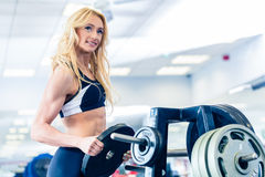 Женщина принимая весы от стойки в спортзале фитнеса Стоковые Изображения RF