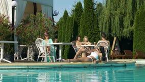Женщина принимая видео- звонок бассейном и группой в составе подросток говоря на другой таблице пока молодая женщина ослабляет на акции видеоматериалы