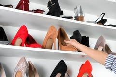 Женщина принимая высоко-накрененный ботинок от включая в набор отложенных изменений блока стоковая фотография rf