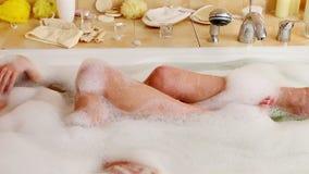 Женщина принимая ноги ванны и мытья пены в ее ванной комнате Система тележки сток-видео