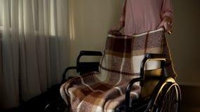 Женщина принимая отсутствующую пустую кресло-коляску, думая о матери, скорба для любимого стоковые изображения rf