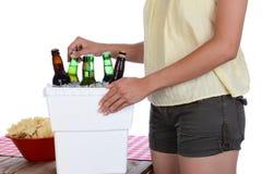 Женщина принимая пиво от комода льда Стоковые Изображения
