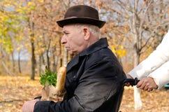 Женщина принимая пожилые неработающие покупки человека стоковое фото