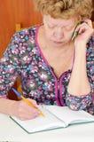 Женщина принимая примечания в блокноте Стоковые Фото