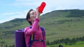 Женщина принимая пролом к питью от бутылки с водой пока пеший туризм акции видеоматериалы