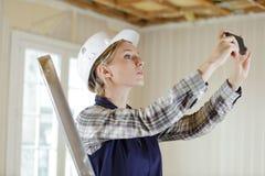 Женщина принимая свойство реновации фотоснимка стоковое изображение rf