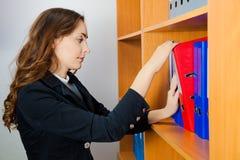 Женщина принимая скоросшиватель Стоковое Фото