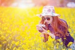 Женщина принимая фото на рапс цветет Стоковая Фотография