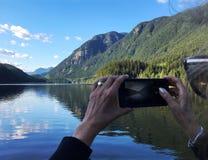 Женщина принимая фото озера горы с мобильным телефоном Стоковые Фотографии RF