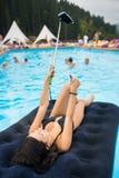 Женщина принимая фото selfie на телефоне и показывая жест больших пальцев руки вверх хорошего класса на тюфяке в бассейне на куро стоковое изображение