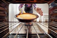Женщина принимая чизкейк из печи в кухне стоковая фотография