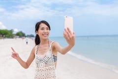 Женщина принимая sefie с мобильным телефоном в пляже песка стоковое фото rf
