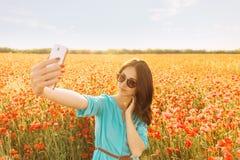 Женщина принимая selfie в красном поле маков стоковые изображения
