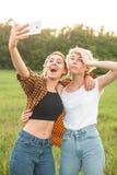 Женщина 2 принимая selfies outdoors Стоковые Фото