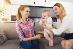 Женщина пришла домой и обнимает ее младенца Медсестра сидит рядом с ей, которое наблюдало детей весь день стоковое изображение