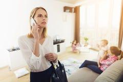 Женщина пришла домой и поговорила на телефоне пока ее дети терли с няней стоковое фото rf