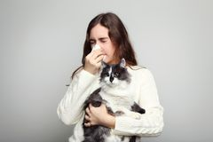 Женщина при аллергия держа кота стоковые фото
