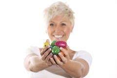Женщина при белокурые волосы держа пасхальное яйцо зайчика шоколада Стоковая Фотография