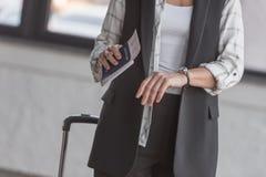Женщина при билет полета смотря вахту Стоковые Фотографии RF