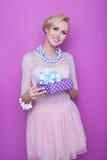 Женщина при большая красивая улыбка держа пурпур присутствующий Рождество праздник подарок стоковое фото rf