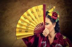Женщина при волосы цветков смотря вас через азиатский вентилятор Стоковые Изображения