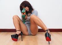 Женщина при высокие пятки направляя с оружием игрушки Стоковое фото RF