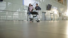 Женщина при 2 дочери вытягивая тележку руки багажа с сумками вдоль залы авиапорта Пассажиры в месте ожидания сток-видео