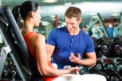 Женщина и личный тренер в спортзале с гантелями Стоковое фото RF