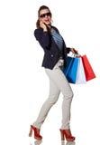 Женщина при женщина хозяйственных сумок говоря на smartphone и идти Стоковое Фото