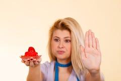 Женщина при измеряя лента держа стоп показа пирожного Стоковые Фотографии RF