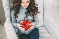 Женщина при длинное вьющиеся волосы держа и смотря сердце подарочной коробки Стоковые Фотографии RF
