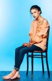 Женщина при искусство тела сидя на деревянном стуле на голубой предпосылке Стоковые Фотографии RF