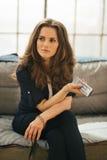 Женщина при дистанционное управление ТВ ослабляя на софе в квартире просторной квартиры Стоковое Фото