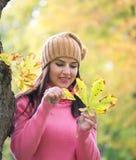 Женщина при лист дуба играя он любит меня или не в парке Стоковая Фотография RF