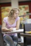 Женщина при кассета сидя на софе в моле Стоковые Фотографии RF