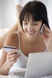Женщина при компьтер-книжка делая приобретение кредитной карточки на мобильном телефоне стоковые фото