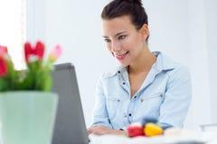 Женщина при компьтер-книжка работая дома Стоковое фото RF
