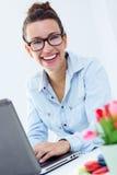 Женщина при компьтер-книжка работая дома Стоковые Изображения RF