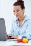 Женщина при компьтер-книжка работая дома Стоковое Фото