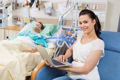 Женщина при компьтер-книжка сидя мужским пациентом внутри Стоковые Изображения RF