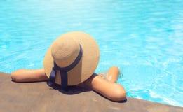 Женщина при коричневая шляпа ослабляя в бассейне с открытым морем в солнце, концепции праздника стоковая фотография rf