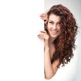 Женщина при коричневое вьющиеся волосы держа шильдик Стоковые Фотографии RF