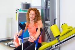 Женщина при костыли сидя на машине тренировки стоковые фотографии rf