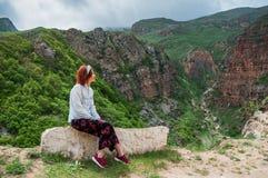 Женщина при красные волосы enjoing сногсшибательный ландшафт гор заволакивает темное небо Стоковые Изображения