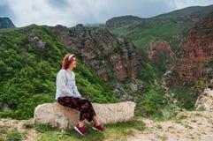 Женщина при красные волосы enjoing сногсшибательный ландшафт гор заволакивает темное небо Стоковая Фотография