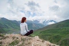 Женщина при красные волосы enjoing сногсшибательный ландшафт гор заволакивает темное небо Стоковые Фото