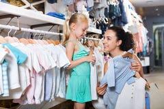 Женщина при малая девушка выбирая голубые одежды Стоковое Изображение RF
