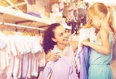 Женщина при малая девушка выбирая голубые одежды Стоковые Изображения RF